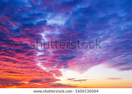 Sunset fire in the sky. Dark blue clouds with red reflections of the setting sun. Scenic sundown cloudscape for background. Dramatic cloudscape at sunset. Beauty in nature. #1606536064