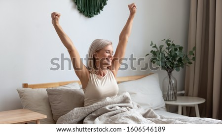 Active happy mature female wake up from good healthy sleep stretching sitting in bed at home, smiling positive senior woman awaken in comfortable bedroom feel optimistic welcome new day #1606546189