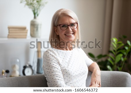 Close up headshot portrait of smiling mature woman in glasses sit on cozy couch at home posing for picture, happy pleased middle-aged elderly female pensioner in spectacles look at camera rest on sofa