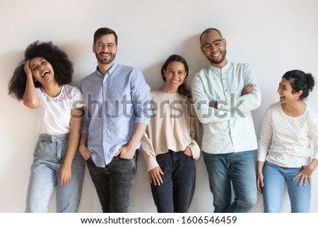Portrait of overjoyed millennial multiethnic friends stand near white wall laughing, multiracial happy young people look at camera posing for picture together, international friendship concept