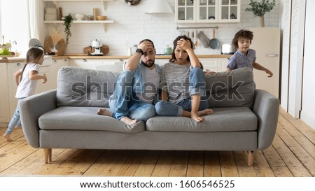 Tired mother and father sitting on couch feels annoyed exhausted while noisy little daughter and son shouting run around sofa where parents resting. Too active hyperactive kids, need repose concept #1606546525