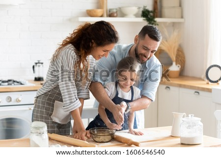 Small adorable kid girl preparing pie with loving caring parents on domestic kitchen, young family enjoy cooking process at home, teaching child, spend weekend together, help, happy parenthood concept #1606546540