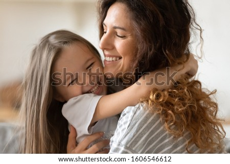 Close up beautiful young mother snuggle little cheerful daughter laughing enjoy moment of tenderness having fun spend time together at home, next generation and offspring, unconditional love concept #1606546612