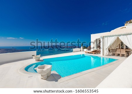 Swimming pool with sea view. White architecture on Santorini island, Greece. Beautiful landscape with sea view. Luxury resort swimming pool in Santorini, Greece. Summer vacation and honeymoon concept #1606553545