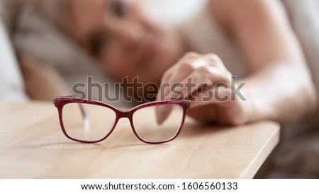 Close up of mature woman lying in bed awaken in morning take glasses from bedside table, senior female wearing spectacles welcome new day wake up in bedroom, elderly eyesight correction concept #1606560133