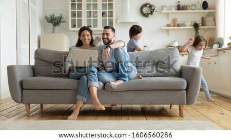 While funny active daughter and son running parents sit on sofa resting using pc online services plan family holiday choose tour booking online apartments, e-commerce usage on weekend at home concept #1606560286