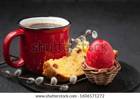 Red Egg in a wicker stand, Easter cake and cup of coffee on black slate dish and painted eggs on the table - traditional Easter breakfast