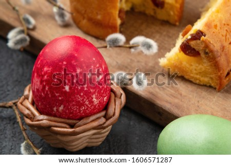 Red Egg in a wicker stand, Easter cake on a cutting board and painted eggs on the table - traditional Easter breakfast