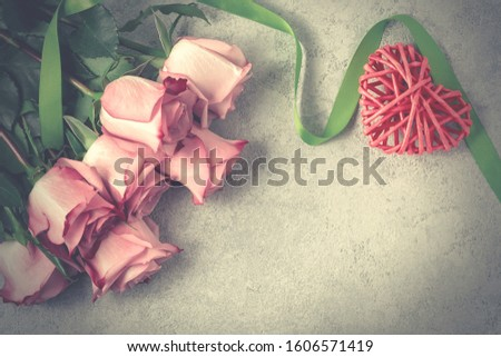 Flower arrangement - bouquet of pink roses and wicker heart on grey concrete surface, template for design or greeting card, place for text, copy space