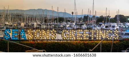 Seasons Greetings sign decorate the Ventura Harbor with the boats and masts in the background at dawn during the Christmas holiday.