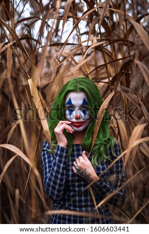 Portrait of a greenhaired girl with joker makeup on a orange leaves reeds background.