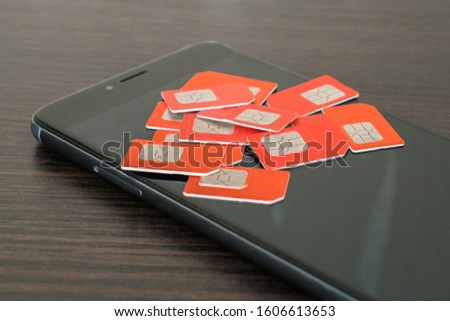 Many red SIM cards are on top of the black screen of the smartphone. Phone chips for mobile communications are on the display of the communicator. Information technology concept. #1606613653
