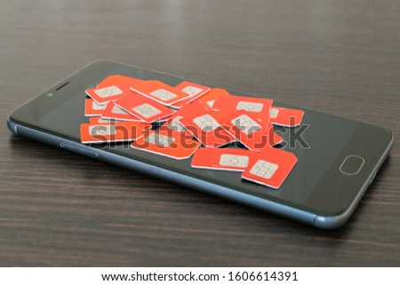 Phone chips for mobile communications are on the display of the communicator. Many red SIM cards are on top of the black screen of the smartphone. Information technology concept. #1606614391