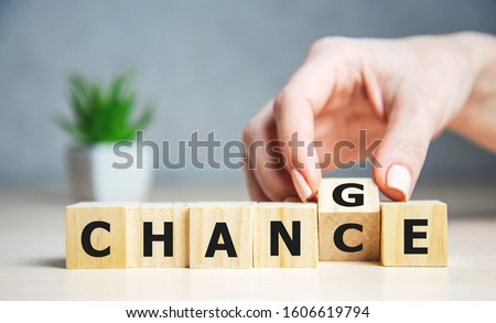 Businesswoman hand holding wooden cube with flip over block CHANGE to CHANCE word on table background. success, strategy, solution, business and Positive thinking concepts Royalty-Free Stock Photo #1606619794