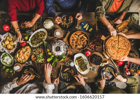 Traditional Turkish family celebration dinner. Flat-lay of people feasting at table with Turkish salads, cooked vegetables, meze starters, pastries and raki drink, top view. Middle Eastern cuisine #1606620157
