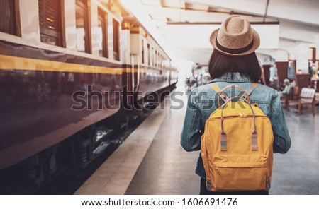 Young asian woman traveler with backpack in the railway, Backpack and hat at the train station with a traveler, Travel concept. Woman traveler tourist walking at train station #1606691476