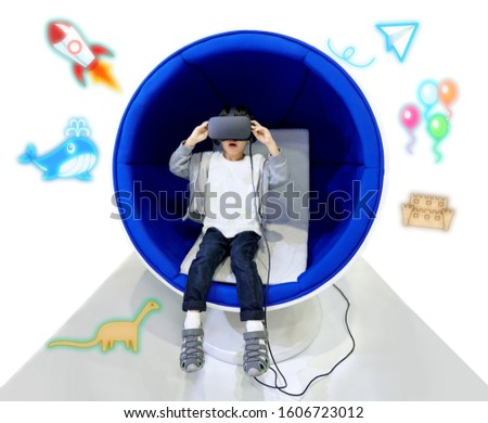 Portrait little asian cute one boy wearing VR or virtual reality goggle headset for learning and entertainment, kid looking excited cartoon virtual imagine background.