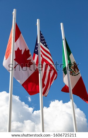 Flags of United States, Mexico, Canada flying together, concept of new NAFTA agreement now known as USMCA in the U.S., CUSMA in Canada or T-MEC in Mexico. #1606725211