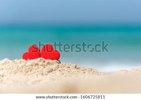 Valentine and Marry Concept.  Two red hearts couple lovers for married wedding in summer day on sand paradise beach, blue background. #1606725811