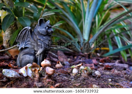 Stone cat gargoyle with bat wings in a enchanting forest  #1606733932