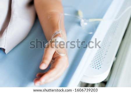 Patients saline, Iv drip, young woman hand with medical drip intravenous needle, give salt water on hospital bed. intravenous therapy (IV) is a therapy that delivers fluids directly into vein. #1606739203