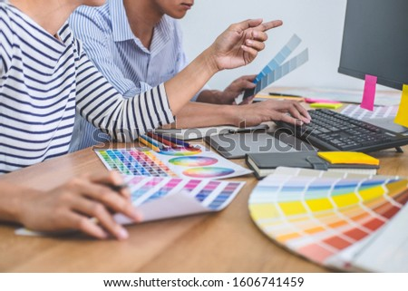 Two colleagues creative graphic designer working on color selection and drawing on graphics tablet at workplace, Color swatch samples chart for selection coloring. #1606741459
