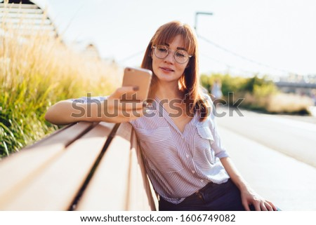 Charming caucasian woman in eyewear red news from social networks on mobile phone sitting on bench during sunny day, beautiful millennial girl user of smartphone browse new app update outdoors  #1606749082