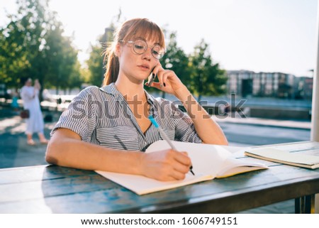 Pensive redhead woman in spectacles writing in notebook noting ideas for publications,attractive caucasian hipster girl student learning outdoors in college campus concentrated on drawing sketch #1606749151