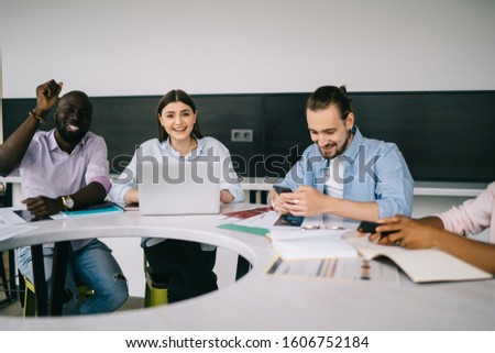 Multiethnic casually dressed staff discussing project and happily smiling at camera while working on project and sitting at circular table in office #1606752184