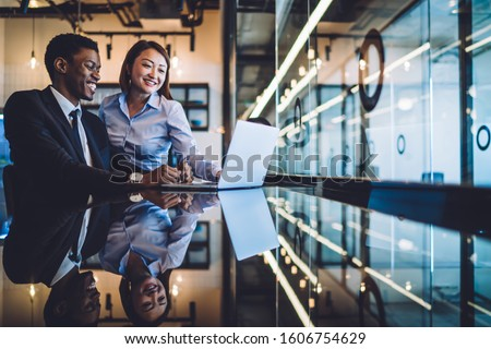 Laughing African American businessman and Asian female colleague watching together funny content on laptop while sitting at reflective counter in office #1606754629