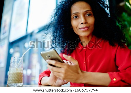 Casually dressed mature black woman in red blouse with afro hairstyle looking away from text messaging via smartphone and smiling #1606757794