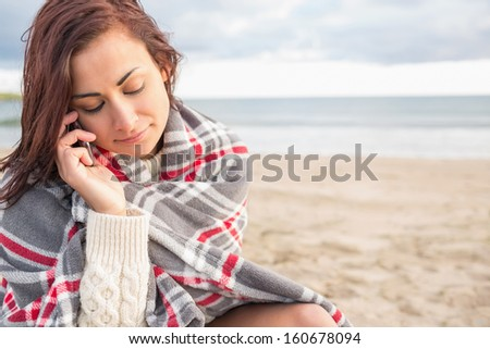 Young woman covered with blanket using cellphone at the beach #160678094
