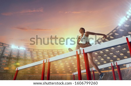 Athlete woman athlete jumps over the barrier at the running track in professional athletics stadium. #1606799260