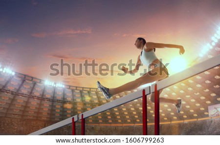 Athlete woman athlete jumps over the barrier at the running track in professional athletics stadium. #1606799263