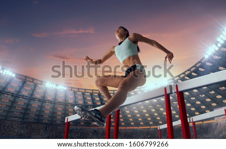 Athlete woman athlete jumps over the barrier at the running track in professional athletics stadium. #1606799266
