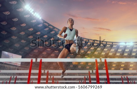 Athlete woman athlete jumps over the barrier at the running track in professional athletics stadium. #1606799269