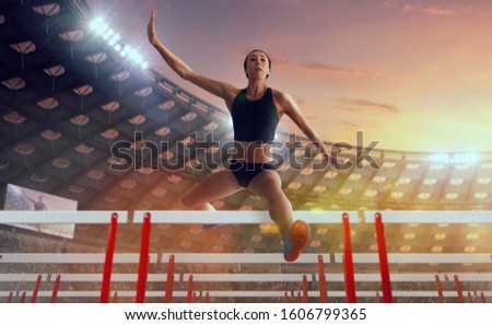 Athlete woman athlete jumps over the barrier at the running track in professional athletics stadium. #1606799365