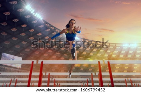 Athlete woman athlete jumps over the barrier at the running track in professional athletics stadium. #1606799452
