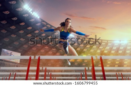 Athlete woman athlete jumps over the barrier at the running track in professional athletics stadium. #1606799455