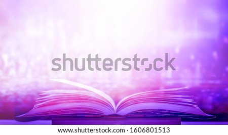 The blurred book that is bewitched with magic, the magic light in the dark, with the bright light shining down as the power to search for knowledge. For research and use as a blurred background #1606801513