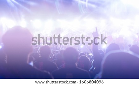 crowd at concert - summer music festival in front of bright stage lights. Dark background, smoke, concert spotlights.people dancing and having fun in summer festival party outdoor #1606804096