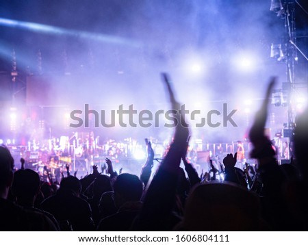 crowd at concert - music festival in front of bright stage lights. Dark background, smoke, concert spotlights.people dancing and having fun in summer festival party outdoor #1606804111
