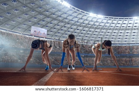 Female athletes sprinting. Women in sport clothes on starting line prepares to run at the running track in professional  athletics stadium. #1606817371