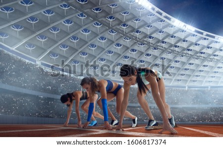 Female athletes sprinting. Women in sport clothes on starting line prepares to run at the running track in professional  athletics stadium. #1606817374