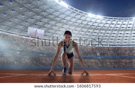 Female athletes sprinting. Women in sport clothes on starting line prepares to run at the running track in professional  athletics stadium. #1606817593