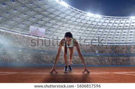Female athletes sprinting. Women in sport clothes on starting line prepares to run at the running track in professional  athletics stadium. #1606817596