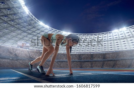 Female athletes sprinting. Women in sport clothes on starting line prepares to run at the running track in professional  athletics stadium. #1606817599