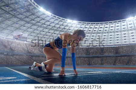 Female athletes sprinting. Women in sport clothes on starting line prepares to run at the running track in professional  athletics stadium. #1606817716