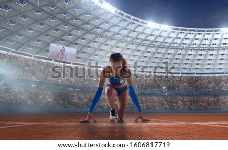 Female athletes sprinting. Women in sport clothes on starting line prepares to run at the running track in professional  athletics stadium. #1606817719