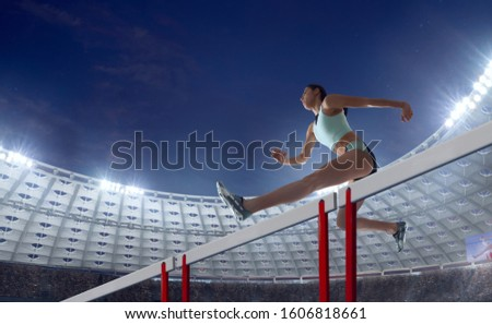 Athlete woman athlete jumps over the barrier at the running track in professional athletics stadium. #1606818661